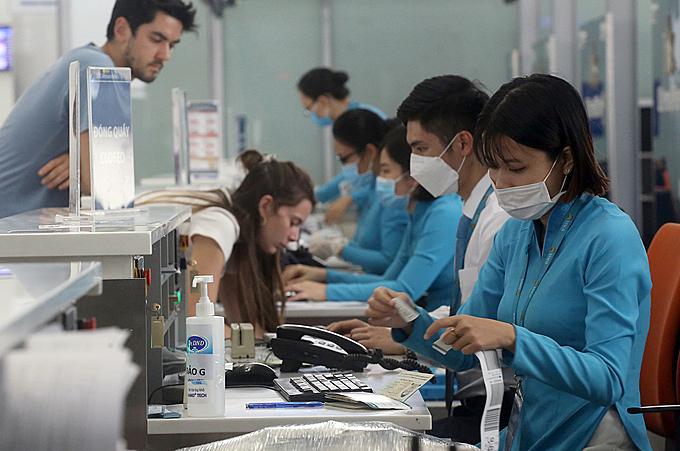 Nhân viênlàm thủ tục check in cho khách tại sân bay Nội Bài thường xuyên tiếp xúc khách nước ngoài không đeo khẩu trang. Ảnh: Bá Đô