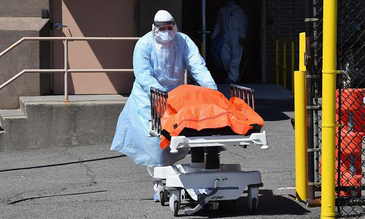 Nhân viên y tế chuyển thi thể bệnh nhân lên một xe tải đông lạnh được dùng làm nhà xác dã chiến ở New York, Mỹ hôm 2/4. Ảnh: AFP.