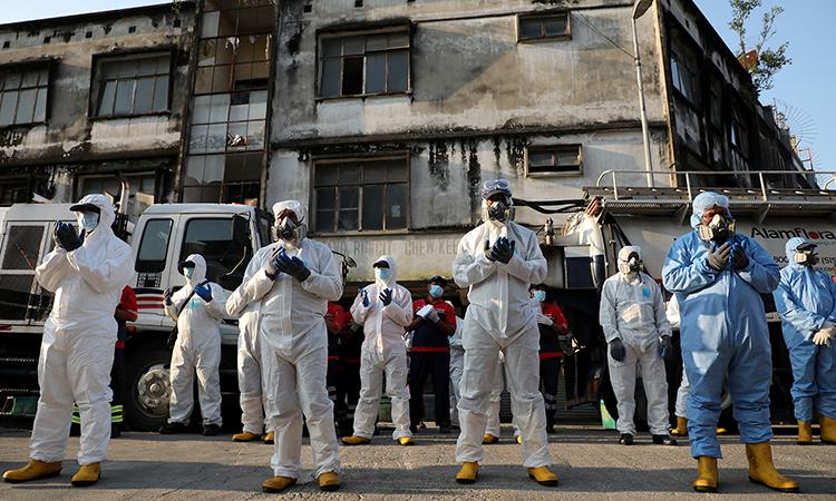 Nhân viên mặc đồ bảo hộ cầu nguyện trước một chiến dịch phun khử trùng ở Kuala Lumpur hôm 1/4. Ảnh: Reuters.