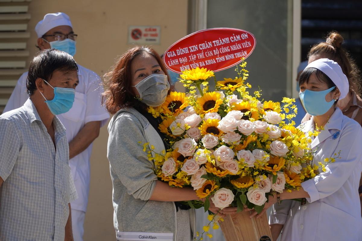 Bà Đặng Thị Lynh Trang, bệnh nhân 34, đại diện các bệnh nhân tặng hoa cảm hơn các y bác sĩ, nhân viên y tế Bệnh Đa khoa Bình Thuận. Ảnh: Việt Quốc.