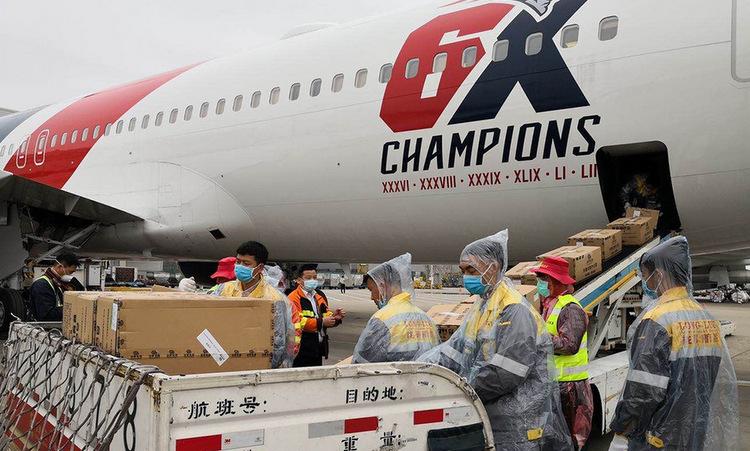 Nhân viên Trung Quốc đưa khẩu trang lên khoang máy bay hôm 2/4. Ảnh: CBS.