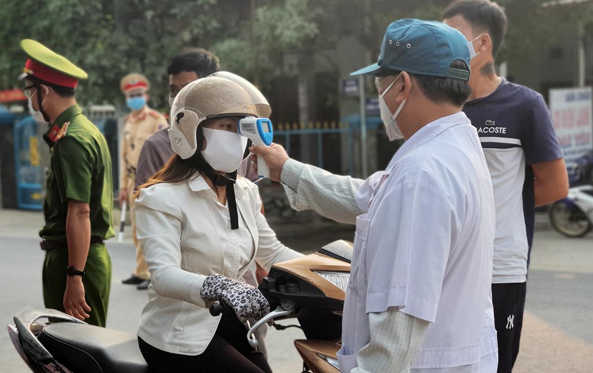 Một người đi vào tỉnh Quảng Nam được lực lượng y tế kiểm tra thân nhiệt. Ảnh: Đắc Thành.