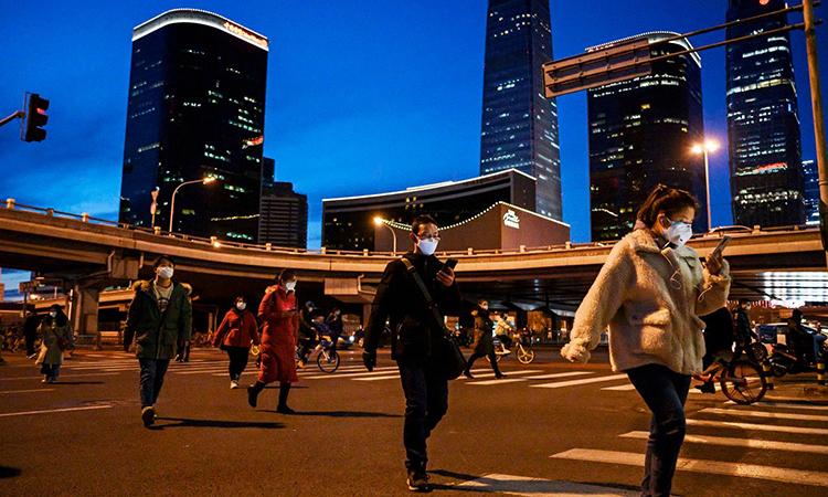 Người dân Trung Quốc đeo khẩu trang đi trên phố Bắc Kinh hôm 12/3. Ảnh: CNN.
