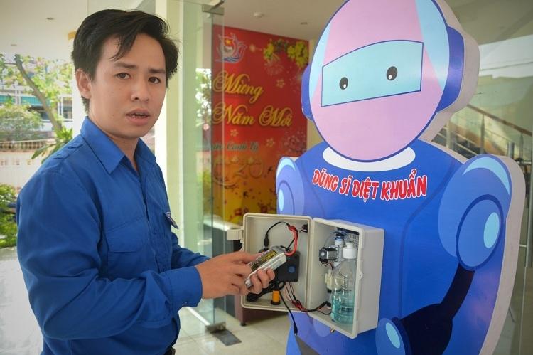 Kĩ sư Võ Trường Tiến bỏ dung dịch rửa tay vào máy. Ảnh: Phạm Linh.