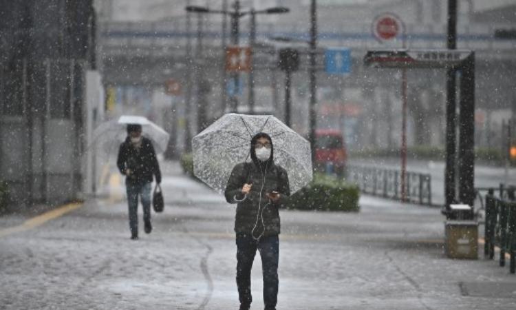 Người dân Nhật Bản đeo khẩu trang khi đi trên đường phố Tokyo hôm 29/3. Ảnh:AFP.