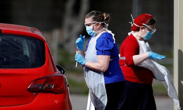 Nhân viên y tế Anh lấy mẫu xét nghiệm cho một tài xế tại Chessington hôm 28/3. Ảnh: Reuters.