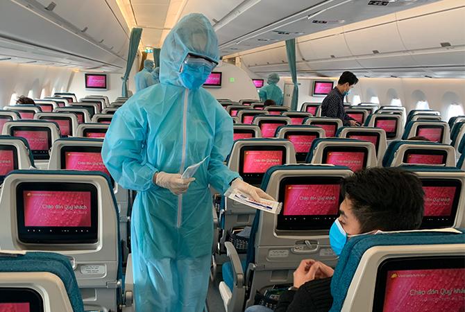 Tiếp viên được trang bị bảo hộ trên chuyến bay từ châu Âu về Việt Nam. Ảnh: VNA