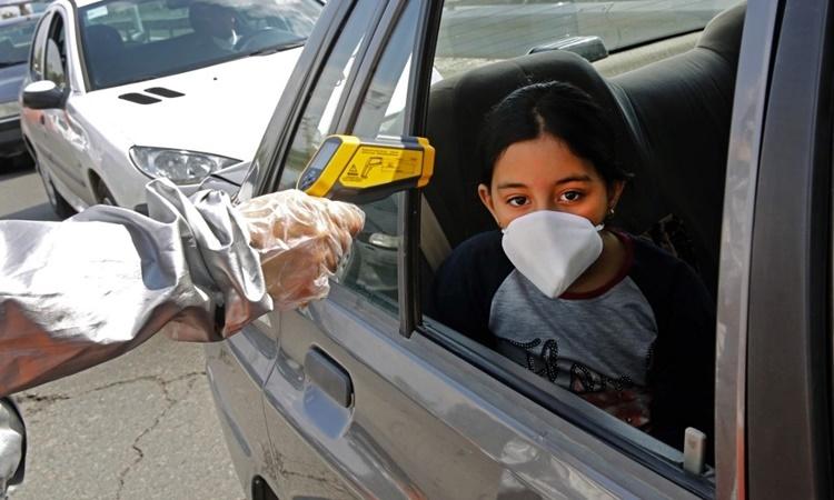 Nhân viên Hội Chữ thập Đỏ Iran kiểm tra thân nhiệt người đi đường bên ngoài thủ đô Tehran ngày 26/3. Ảnh: AFP.