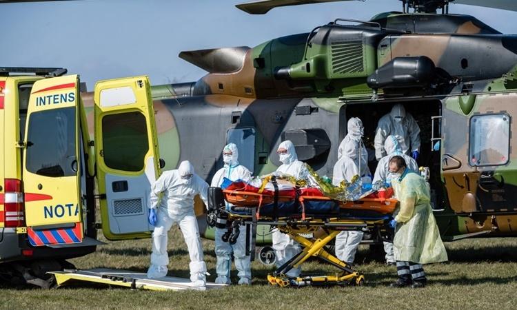 Nhân viên y tế Đức chăm sóc một bệnh nhân nhiễm nCoV người Pháp tại sân bay gần thành phố Nordhausen ngày 2/4. Ảnh: AFP.