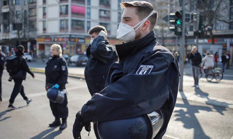 Cảnh sát đeo khẩu trang khi giải tán cuộc tuần hành tự phát tại quận Kreuzberg của thủ đô Berlin, Đức ngày 28/3. Ảnh: AFP.
