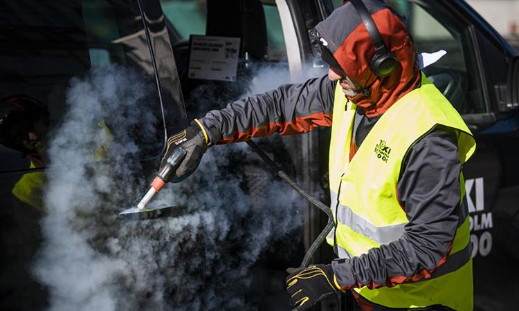 Người đàn ông vệ sinh và phun hóa chất tẩy trùng cho xe taxi để ngăn nCoV lây lan tại Stockholm, Thụy ĐIển ngày 2/4. Ảnh: AFP.