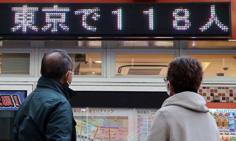 Hai người dân Tokyo nhìn bảng thông báo số ca nhiễm nCoV mới của thành phố hôm 5/4. Ảnh: Reuters.