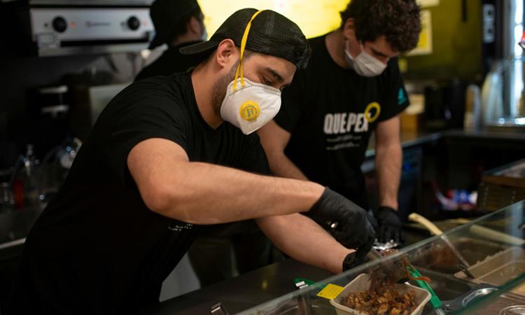 Nhân viên một nhà hàng ở Barcelona đang chuẩn bị đồ ăn tặng y bác sĩ hôm 4/4. Ảnh: AFP.