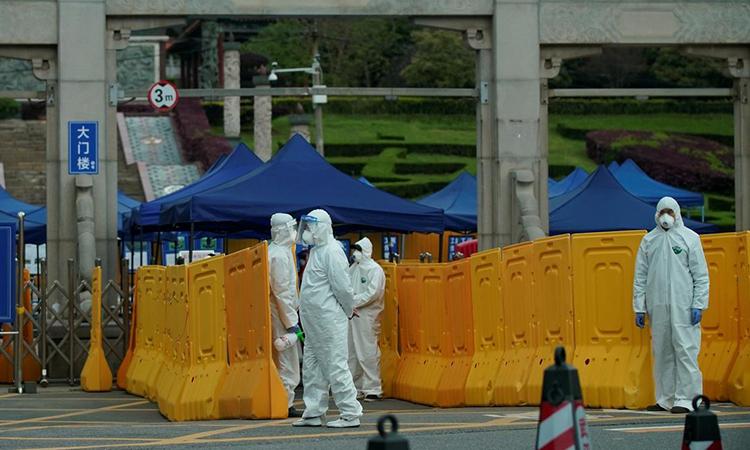 Nhiều người mặc trang phục bảo hộ bên ngoài một nghĩa trang ở Vũ Hán, tỉnh Hồ Bắc, Trung Quốc hôm 1/4. Ảnh: Reuters.