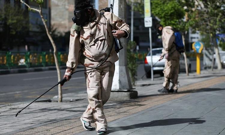 Tình nguyện viên mặc đồ bảo hộ phun khử trùng đường phố Tehran, Iran hôm 3/4. Ảnh: Reuters.