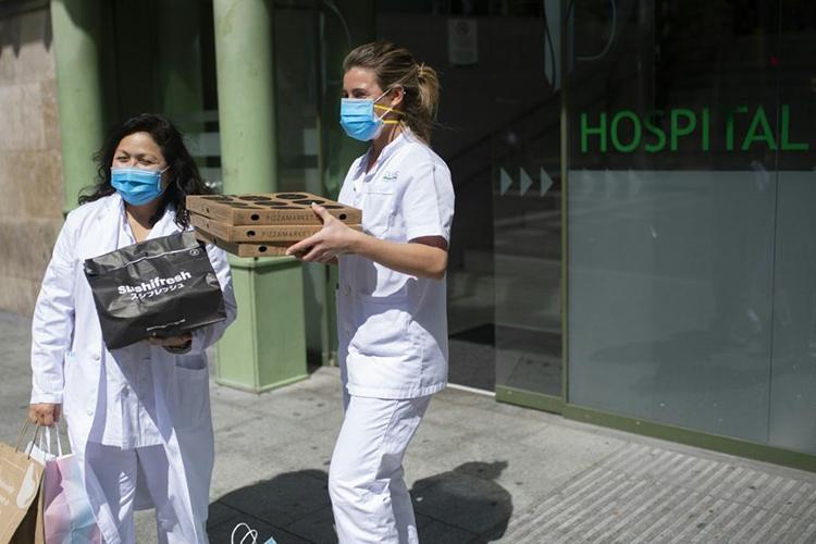 Hai nữ y tá nhận đồ ăn từ Daniel Valks. Ảnh: AFP.