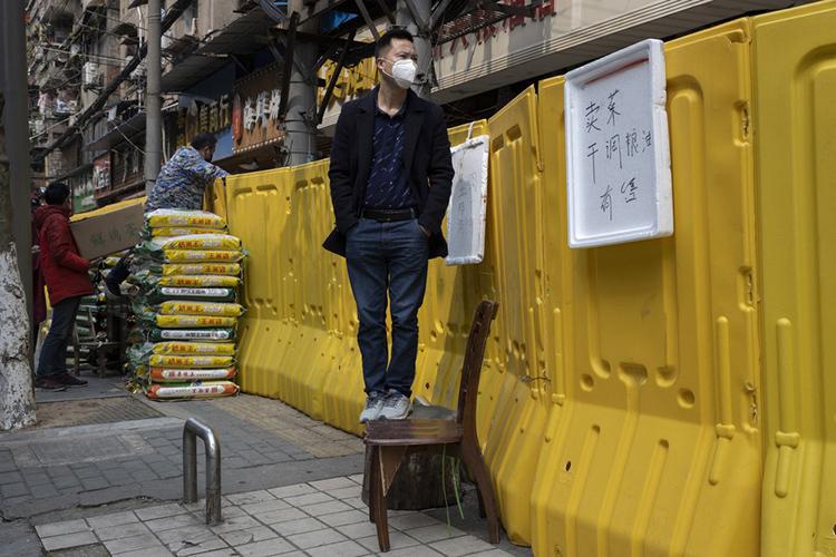 Một người đàn ông đứng bên hàng rào của một chung cư ở Vũ Hán hôm 3/4. Ảnh: AP