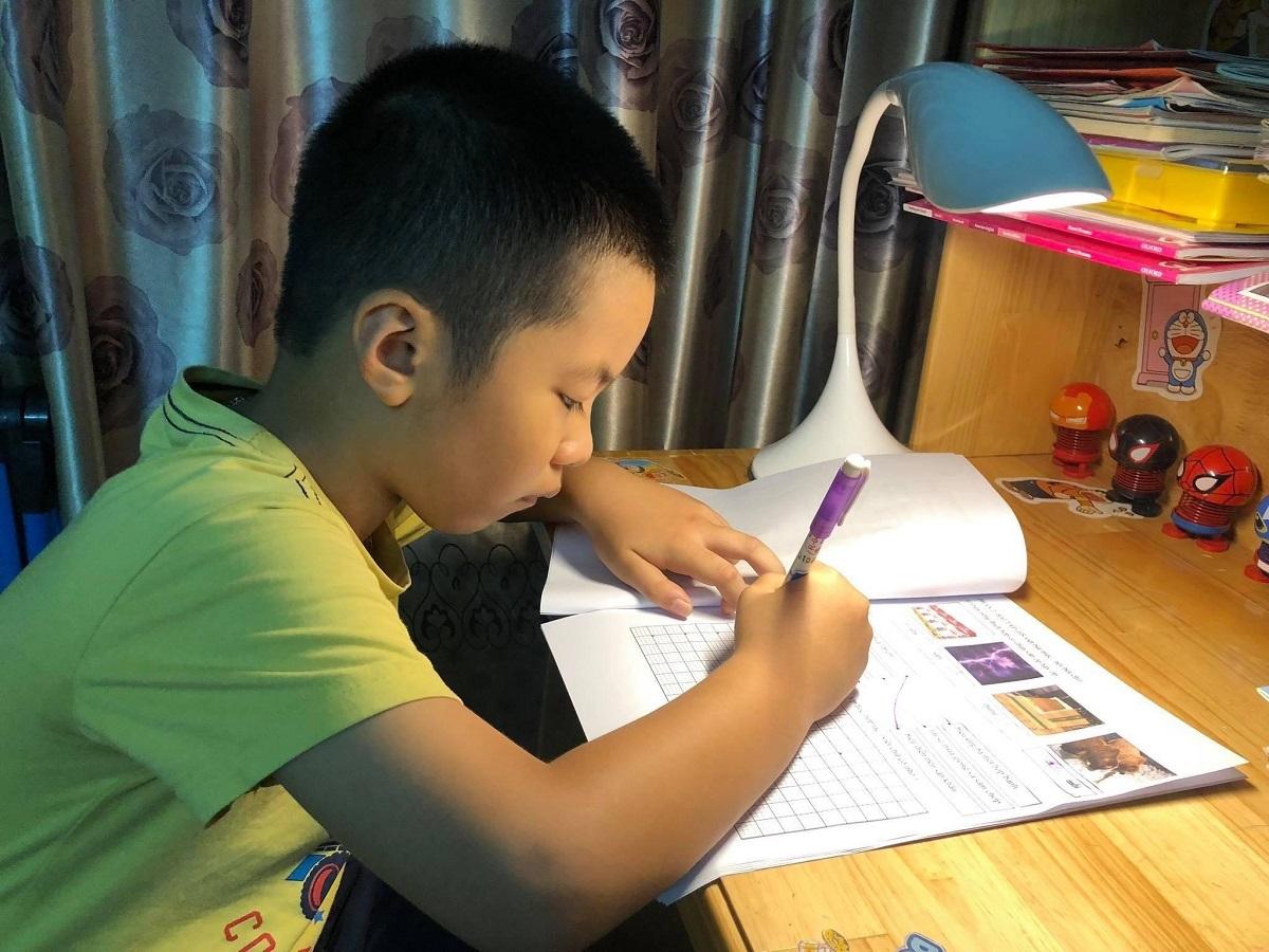 Học sinh lớp 1 trường Tiểu học Hồng Hà (quận Bình Thạnh, TP HCM) làm bài tập do cô giáo giao qua phần mềm dạy học trực tuyến. Ảnh: Thảo Nguyên.
