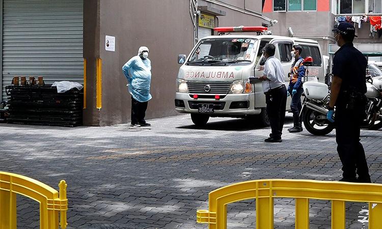 Xe cứu thương đỗ bên ngoài khu ký túc xáWestlite bị cách ly hôm 6/4. Ảnh: Reuters.