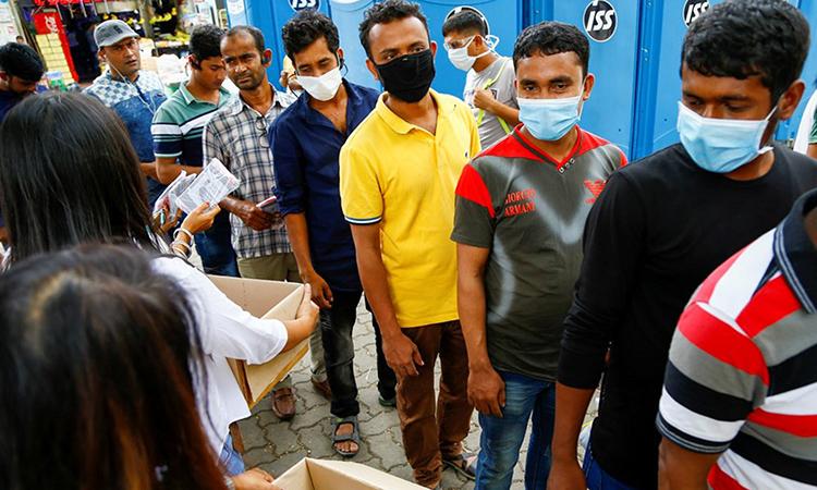 Công nhân Bangladesh xếp hàng chờ nhận khẩu trang tại khu ký túc xa S11. Ảnh: Reuters.