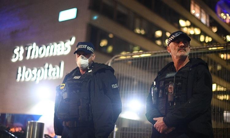 Cảnh sát đứng gác bên ngoài bệnh viện St Thomas, nơi Thủ tướng Anh Boris Johnson đang được điều trị tối 6/4. Ảnh: Reuters.