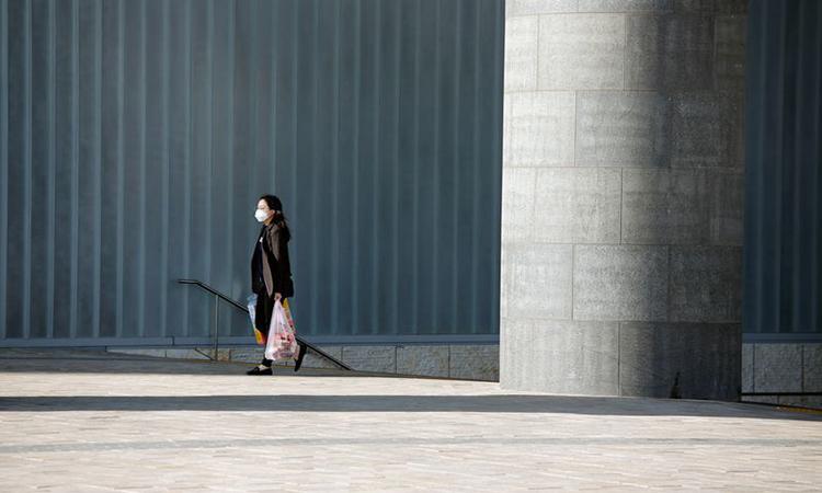 Một phụ nữ đeo khẩu trang trên đường phố Seoul, Hàn Quốc hôm 3/4. Ảnh: Reuters.