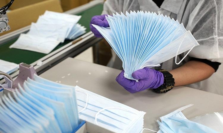 Công nhân kiểm tra khẩu trang y tế trong dây chuyền sản xuất ở Đài Loan hôm 6/4. Ảnh: Reuters.
