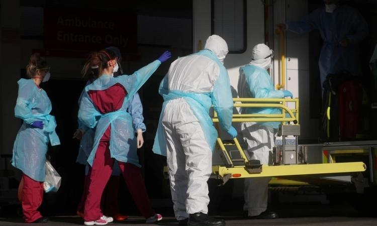 Nhân viên y tế Anh mặc đồ bảo hộ vận chuyển bệnh nhân tại Bệnh viện St Thomas ở London hôm 31/3. Ảnh:Reuters.