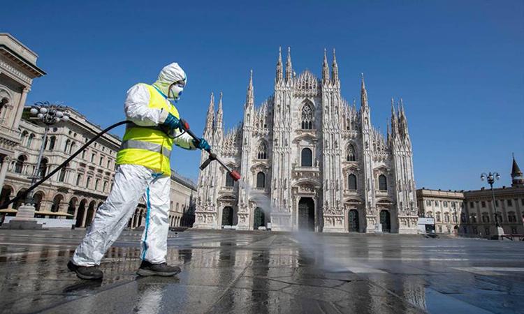 Nhân viên phun thuốc khử trùng phía trước nhà thờ ở thành phố Milan hôm 31/3. Ảnh: AP.