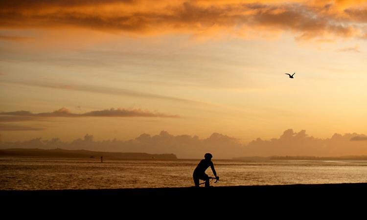 Chỉ có một người đạp xe trên bờ biểnAuckland hôm 26/3. Ảnh: AFP.