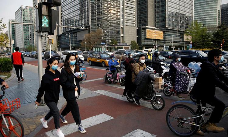 Người dân đeo khẩu trang trên một con phố ở Bắc Kinh, Trung Quốc trong giờ cao điểm ngày 8/4. Ảnh: Reuters.