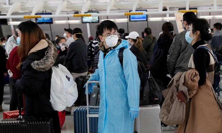 Hành khách xếp hàng lên một chuyến bay của hãng hàng không Air China khởi hành từ New York ngày 13/3. Ảnh: Reuters.