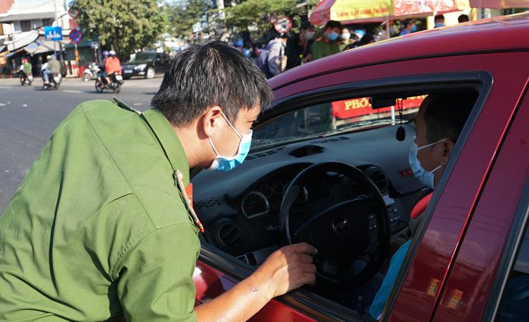 Công an quận Thủ Đức kiểm tra thông tin ôtô cá nhân vào thành phố, nhắc nhở người dân đeo khẩu trang tại cầu Vĩnh Bình (cửa ngõ TP HCM - Bình Dương). Ảnh: Mạnh Tùng