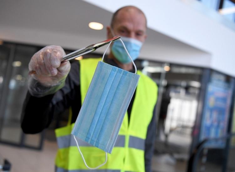 Nhân viên siêu thị phát khẩu trang cho người đến mua sắm ởVienna, Áo ngày 6/4. Ảnh: AFP.
