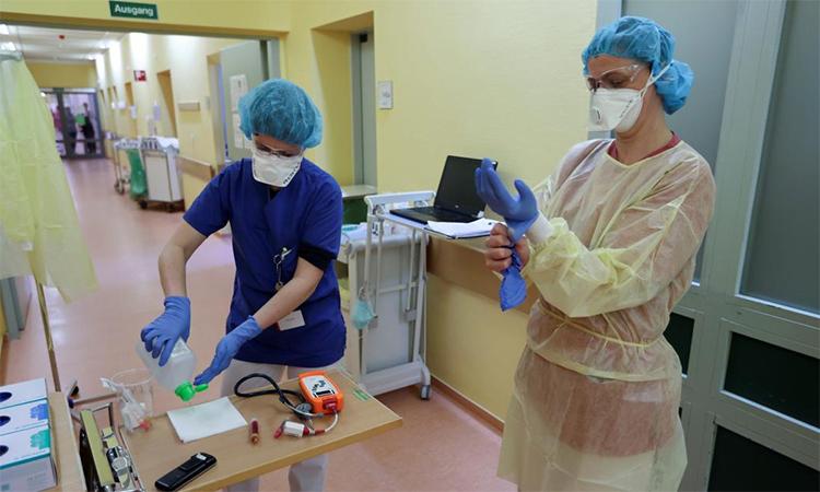 Nhân viên y tế dùng dung dịch sát trùng trong lúc mặc quần áo bảo hộ trước khi chăm sóc bệnh nhân nhiễm nCoV tại khu cách ly của Bệnh viện Cộng đồng Havelhoehe ở Berlin, Đức ngày 6/4. Ảnh: Reuters.