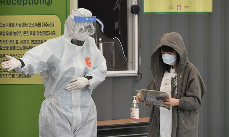 Một nhân viên chính quyền thành phố Seoul mặc đồ bảo hộ hướng dẫn người tới trạm lấy mẫu xét nghiệm nCoV tại Tổ hợp Thể thao Jamsil ngày 3/4. Ảnh: AFP.