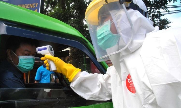 Nhân viên y tế Indonesia kiểm tra thân nhiệt một tài xế ởBogor, tỉnh Tây Java, hôm 8/4. Ảnh: Reuters.