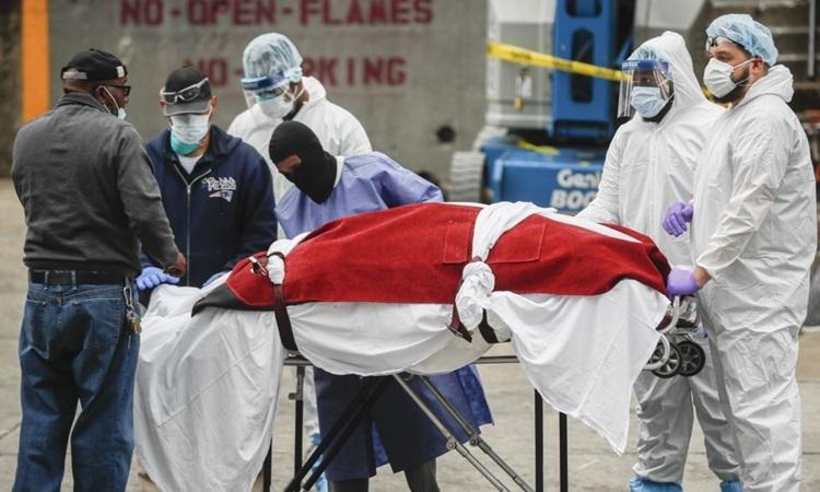 Nhân viên y tế Mỹ di chuyển một thi thể từ xe tải đông lạnh tại bệnh viện ở New York hôm 31/3. Ảnh: AP.