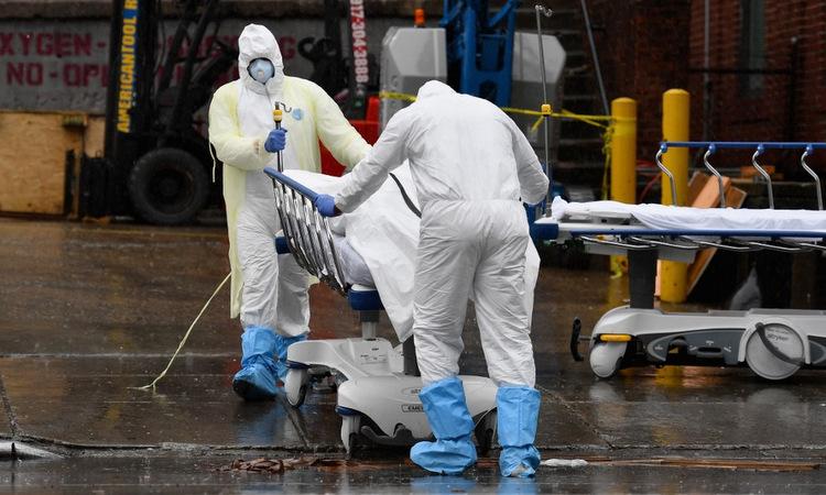 Nhân viên y tế Mỹ đưa thi thể bệnh nhân ra xe đông lạnh tại New York hôm 9/4. Ảnh: AFP.