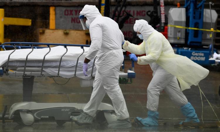 Nhân viên y tế đưa thi thể bệnh nhân Covid-19 ra xe đông lạnh ở New York hôm 9/4. Ảnh: AFP.