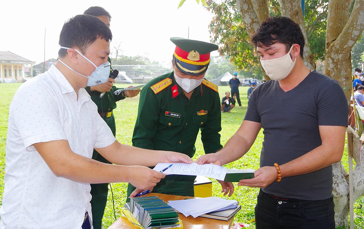Người dân (bên phải) nhận giấy chứng nhận hoàn thành cách ly. Ảnh: Văn Đức