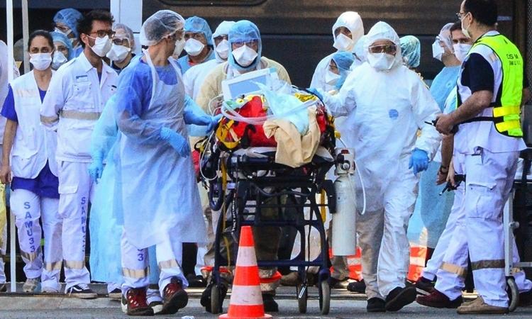 Nhân viên y tế di chuyển người nhiễm nCoV tại Pháp ngày 10/4. Ảnh: AFP.