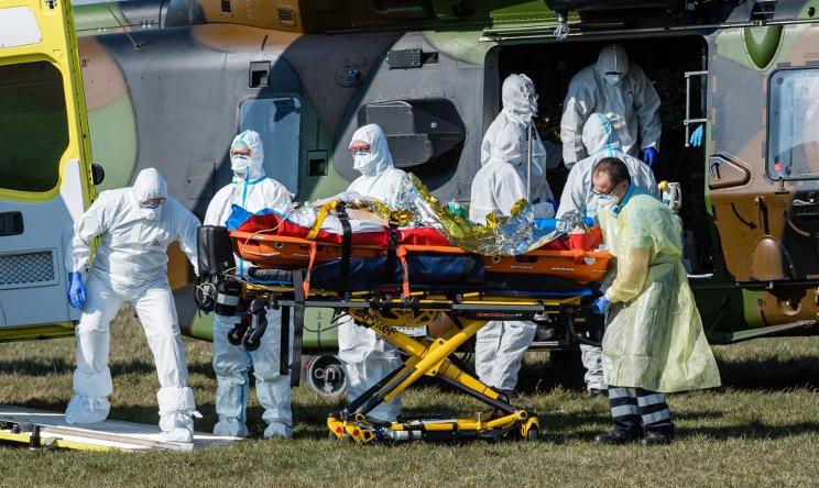 Nhân viên y tế Đức đón bệnh nhân Covid-19 từ Pháp hôm 2/4. Ảnh: AFP.