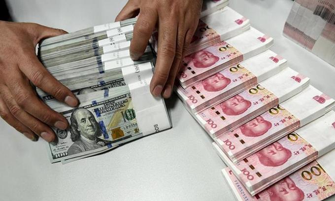 Nhân viên kiểm tiền USD và tệ tại một chi nhánh của Ngân hàng Trung Quốc ở tỉnh Sơn Tây tháng 1/2016. Ảnh: Reuters.