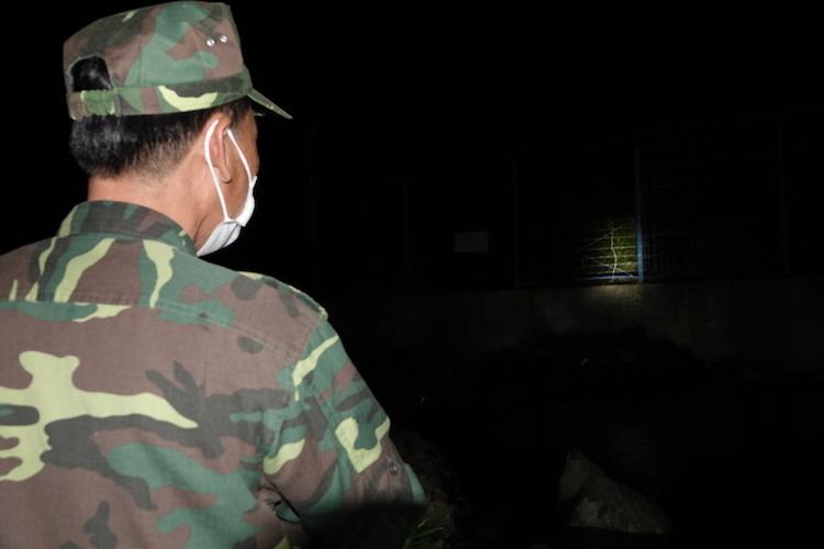 Bộ đội Biên phòng dùng đèn pin chiếu sáng, quan sát lối mở ở đường biên trong ca trực đêm. Ảnh: Hoàng Thuỳ