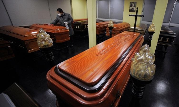 Nhân viên nhà xác lau chùi quan tài giữa đại dịch Covid-19 ởConcepcion, Chile tháng trước. Ảnh: Reuters.