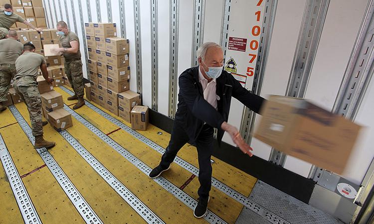 Thống đốc Asa Hutchinson (phải)giúp lực lượng Vệ binh Quốc gia chuyển thùng đồ bảo hộ y tế lên xe tải ở bang Arkansas tháng này. Ảnh: AP.