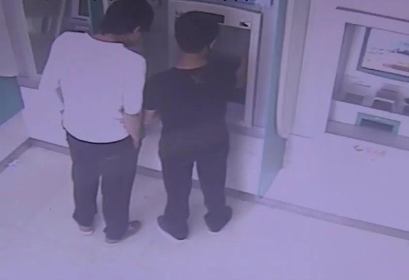 Hai thanh niên rút tiền từ thẻ của Cường. Ảnh: CCTV.