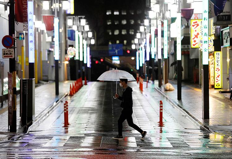 Nam thanh niên đi qua một đường phố Tokyo vắng vẻ hôm 16/4. Ảnh: Reuters