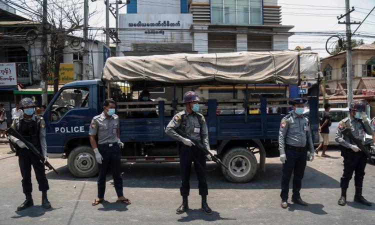 Cảnh sát Myanmar đeo khẩu trang đứng canh trước nhà tù Insein ở Yangon trước khi phóng thích tù nhân vào hôm nay. Ảnh: AFP.